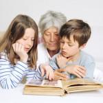 Kinder und Oma schauen ein Fotoalbum an